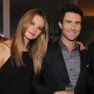 Adam Levine keeps a tight hold on fiancee Behati Prinsloo as they jet off together